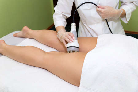 Photo pour The spa beautician holds the RF-lifting maniple in his hand and performs the procedure for problem areas on the thigh. - image libre de droit