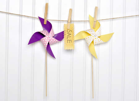 Vibrant Summer Sale Concept Pinwheels with Sale Sign on Clothesline.