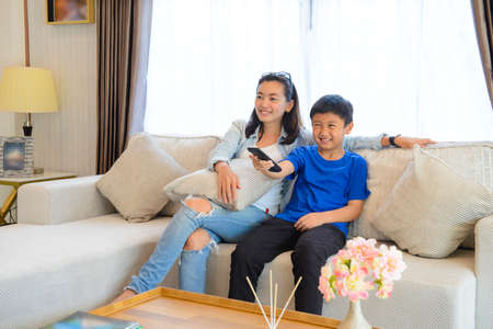 Photo pour Mother and her son are watching tv while sitting on a couch - image libre de droit