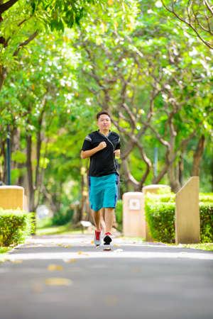 Foto de Young man in sports clothing jogging in park with headphone - Imagen libre de derechos