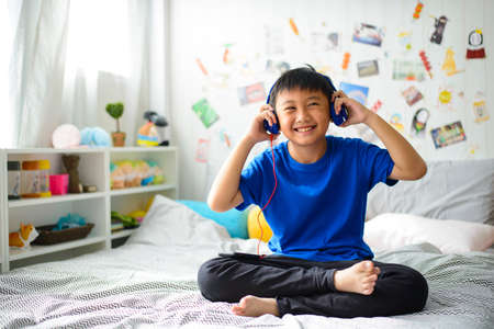 Photo for Little asian boy using headphones and smiling happy while listening music - Royalty Free Image