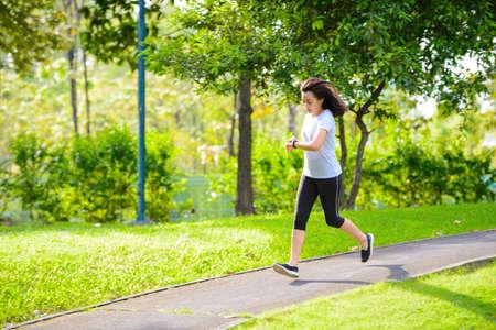 Foto de Young asian woman running in a city park and looks at the smart watch - Imagen libre de derechos