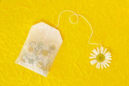 Bag of chamomile tea over yellow handmade paper - concept