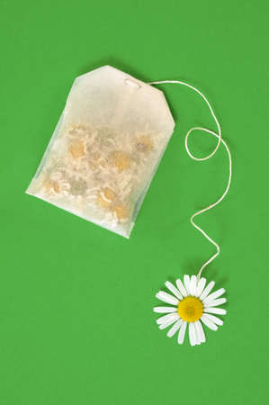 Bag of chamomile tea over green background - concept