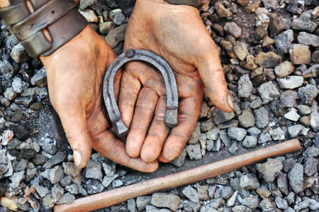 Detail of dirty hands holding horseshoe - blacksmith