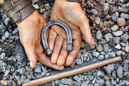 Detail of dirty hands holding horseshoe - blacksmith