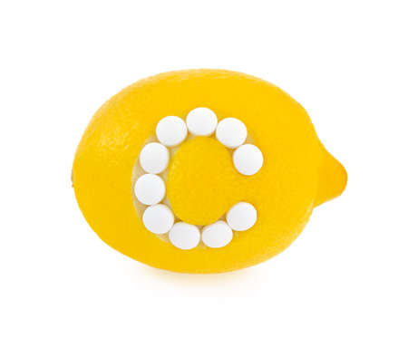 Lemon with vitamin c pills over white background - concept