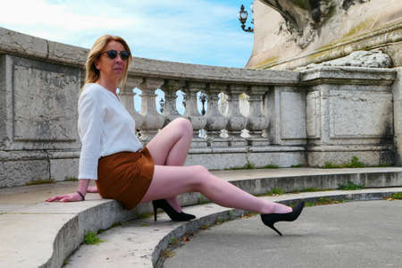 Photo pour Pretty blonde woman in skirt, sitting on stone steps in the city. Legs elongated with high heels. - image libre de droit