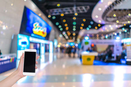 Foto de Hand holding mobile phone with indoor cars exhibition show blurred background and bokeh light, Social network, internet - Imagen libre de derechos