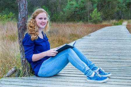 European teenage girl reading book on wooden path in forest