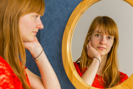 Caucasian redhead teenage girl looking in mirror