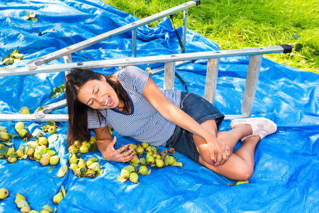 Foto für Young fallen woman lying injured on ground near ladder and pears - Lizenzfreies Bild