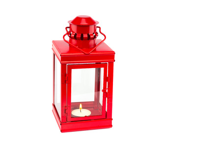 Red metal lantern with burning tealight on white