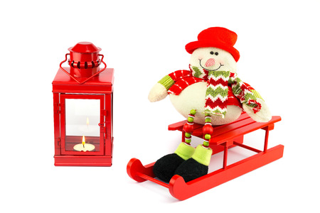 Snowman on sledge with red lantern burning