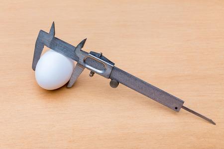 Vernier caliper measuring white chicken egg on wood
