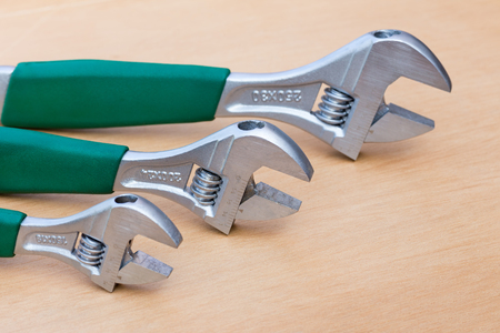 Three adjustable wrenches of different size standing upright on wood