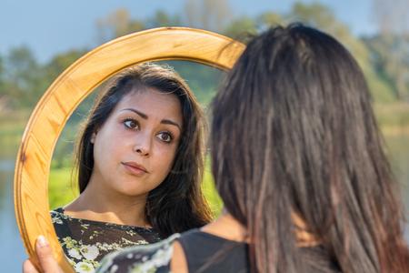 Foto de Young woman looking at mirror image in nature - Imagen libre de derechos