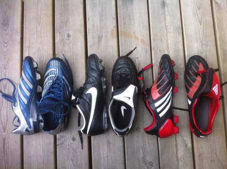 Three pairs of football boots from Adidas and Nike.
