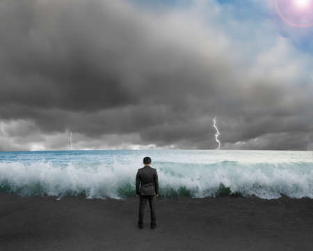 Businessman standing toward waves and cludy sky with Lightning , thunder to challenge dangerous situation