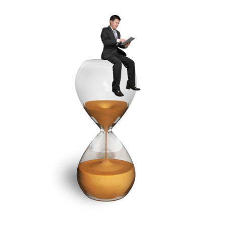 man using tablet and sitting on hourglass with white background