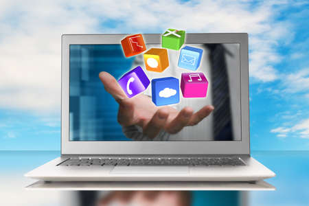 hand stretch out laptop screen with app blocks and sky background
