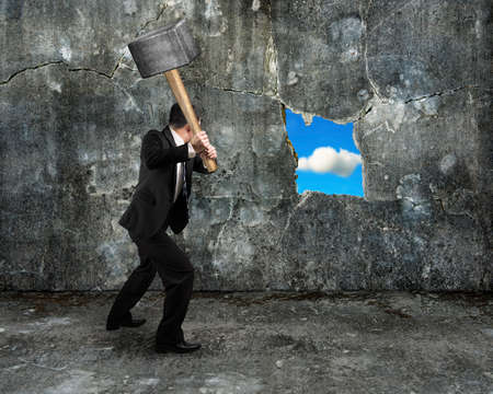 businessman hold sledgehammer cracking big hole discovered natural sky on concrete wall background