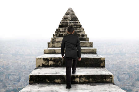 Businessman climbing the old concrete stairs with urban scene background