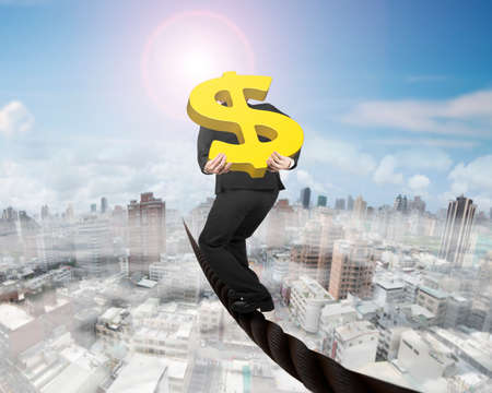 Businessman carrying 3D gold dollar sign balancing on a wire, with sky sun mist cityscape background.