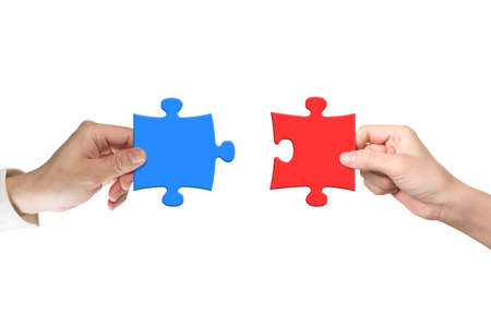 Foto de Man and woman hands assembling different color puzzle pieces, isolated on white. Teamwork concept. - Imagen libre de derechos