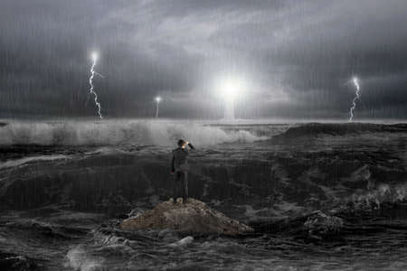 Photo pour Man on rock gazing at lighthouse in the ocean with storm, thunder, lightering and waves in dark - image libre de droit