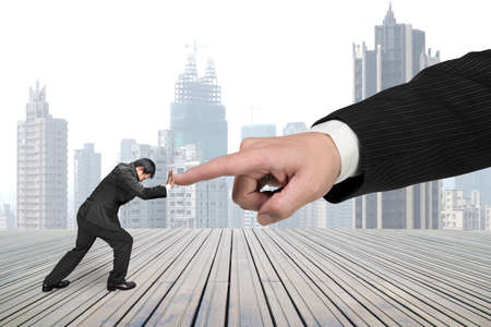 Photo pour Small man pushing against big other hand forefinger on wooden floor and city skyscraper background. - image libre de droit