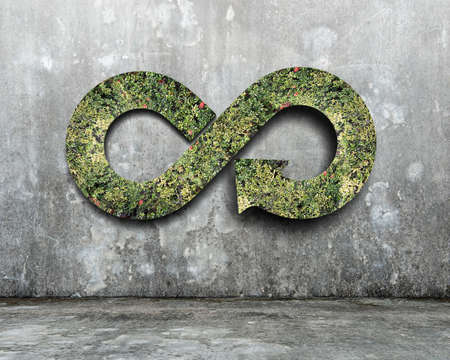 Photo pour Green circular economy concept. Arrow infinity symbol with grass on concrete wall. - image libre de droit