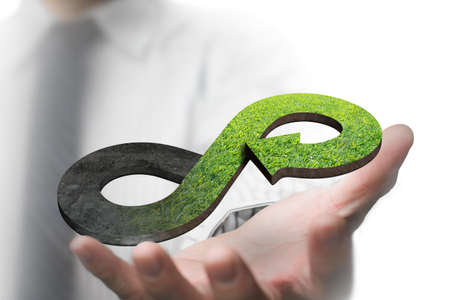 Photo pour Green circular economy concept. Hand showing arrow infinity symbol with grass texture. - image libre de droit