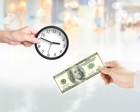 Buying time concept. Hand holding dollar banknote to buy clock from another hand holding.