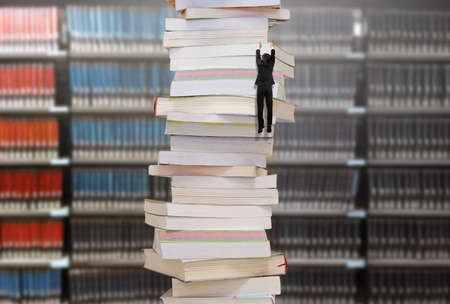 Photo pour Climbing businessman hang on high stack of books with blur bookshelfs background. Reading and learning a mountain of new knowledge concept. - image libre de droit