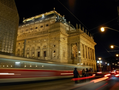 Night view on the National Theatre in Prague from the National Avenue. The old tram leaving the station.