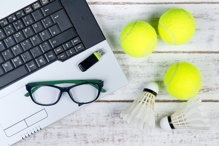 Top view of laptop, Sports Equipment, Tennis ball, Shuttlecock, glasses and USB flash drive on the Sports administration white table.Business concept.
