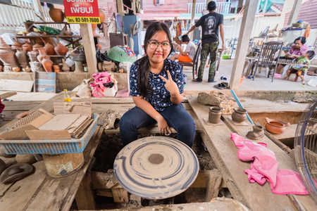 Nonthaburi, Thailand - December, 17, 2017 : Unidentified name tourist teenage woman learning making shaping a jar on the spinning by clay at Koh Kret Nonthaburi, Thailand.