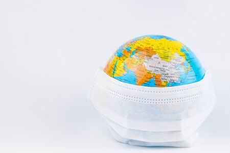 Foto de Surgical Face Mask and Globe model. Coronavirus Concept. Medical Face Mask For Stopping The Spread of Flu Virus. Surgical mask with rubber ear straps. Standard surgical mask to cover the mouth and nose. Covid-19. - Imagen libre de derechos