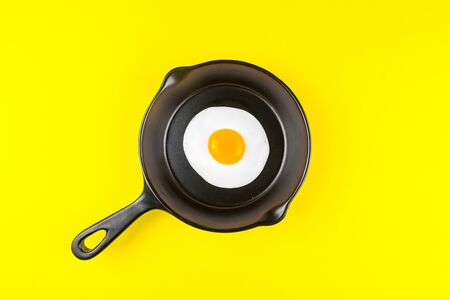 Photo for Frying pan with fried egg isolated on a yellow background viewed from above. - Royalty Free Image