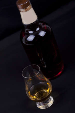 glass and bottel of whisky on a black background