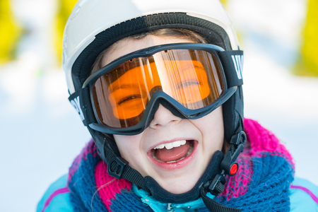 Ski, skier girl, winter vacation, snow, skier, sun and fun - portrait of girl in goggles enjoying skiの写真素材