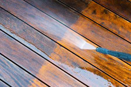 Foto de cleaning terrace with a power washer - high water pressure cleaner on wooden terrace surface - Imagen libre de derechos