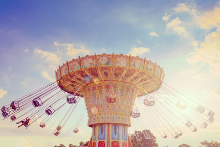 Photo pour Wave Swinger ride against blue sky, vintage filter effects - a swinging carousel fair ride at dusk - image libre de droit