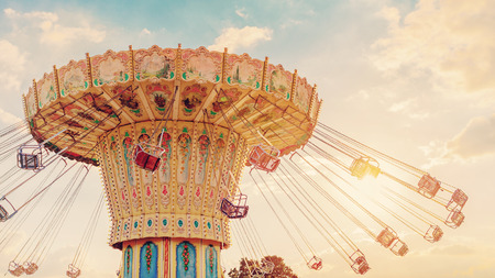 Photo pour carousel ride spins fast in the air at sunset - vintage filter effects - a swinging carousel fair ride at dusk - image libre de droit