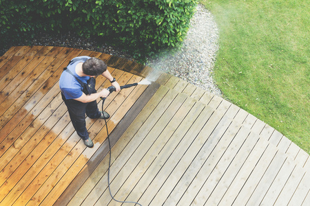 Photo pour cleaning terrace with a power washer - high water pressure cleaner on wooden terrace surface - image libre de droit