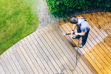 Foto de man cleaning terrace with a power washer - high water pressure cleaner on wooden terrace surface - Imagen libre de derechos