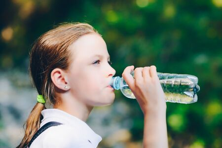 Photo pour Girl drinking water outdoors - very shallow depth of field - image libre de droit