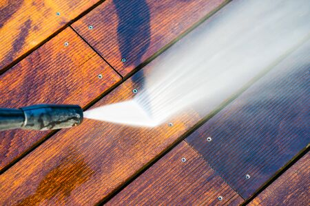 Photo for cleaning terrace with a power washer - high water pressure cleaner on wooden terrace surface - Royalty Free Image
