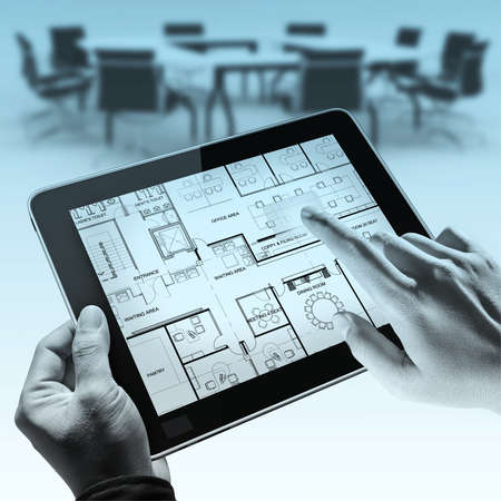 business hands point on interior layout plan on tablet computer as meeting concept